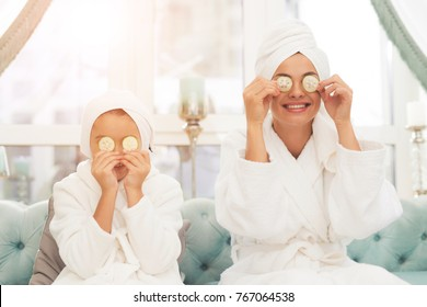 Photo of mother and daughter in white bathrobes. They are sitting on the couch and applying pieces of cucumber to their eyes. Their hair is wrapped in a white bath towel.