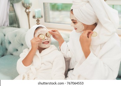 Photo of mother and daughter in white bathrobes. They are sitting on the couch and applying pieces of cucumber to their eyes. Their hair is wrapped in a white bath towel. They have cucumber mask.
