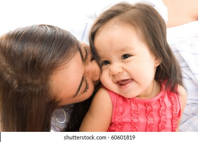 photo of a Mother kissing her daughter .