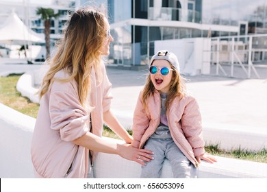 Photo of mother with little daughter are playing outdoor. Little girl sitting with open mouse and smile. Sunny bright day.
