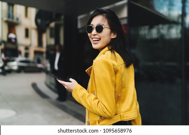 Photo in motion of a smiling asian woman with long dark hair in yellow leather jacket holding a mobile phone while walking the street. Cheerful student girl chatting online by a smartphone