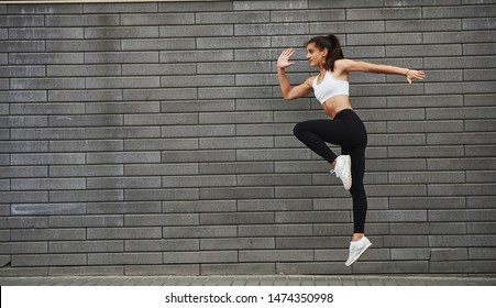 Photo in motion. Young sportive brunette with slim body shape against brick wall in the city at daytime.