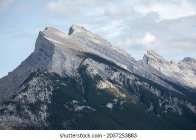 Photo of the Mount Rundle in Alberta. This was taken on a summer day.  There is some clouds in the sky.