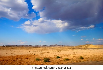 Photo from a moving car - beautiful scenery of colorful sand, dunes and rare plants against the background of blue sky in Kyzyl Kum (Kyzylkum, Qyzylqum, Qizilqum) desert, Uzbekistan, Central Asia
