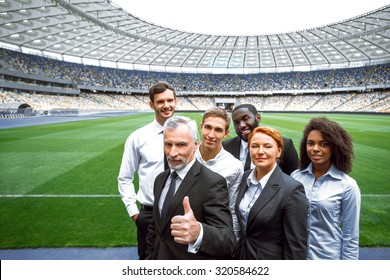 Photo of multi ethnic business group. Mixed race business team standing on modern sport track. Accent on leader of group. Stadium as a background