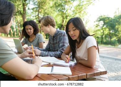 Photo of multiethnic group of concentrated young students sitting and studying outdoors while using laptop. Looking aside.
