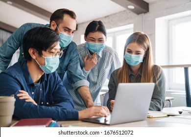 Photo of multinational pleased students in medical masks studying with laptop at classroom
