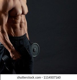 Photo of muscular man exercising with heavy dumbbells in the gym. Sportsman having clear muscles relief. Sport lifestyle. Regular gym trainings, exercising with dumbbells and trainer. Fit sporty body.