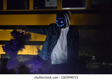 Photo of my friend with an anarchy mask on, in the dark, lit up by high beam lights.