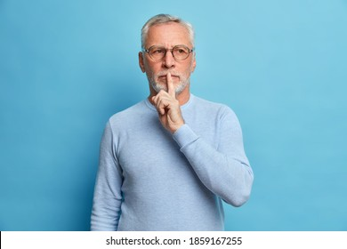 Photo of mysterious bearded man makes silence gesture has thoughtful expression asks to be quiet tells secret wears casual jumper and optical glasses isolated over blue background. Shh dont speak