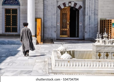 Photo of native man in long coat walking away to building made of stone and marble in Ashgabat in Turkmenistan.