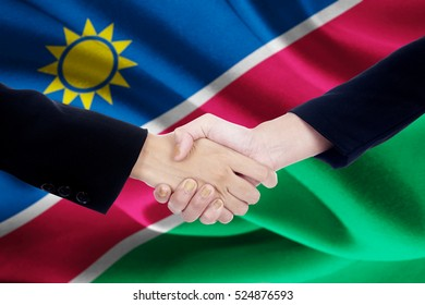 Photo of a negotiation handshake with two worker hands, closing a meeting and shaking hands with Namibia flag background