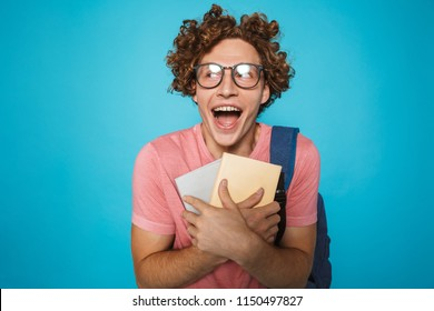 Photo of nerd student guy with curly hair wearing glasses and backpack laughing and holding books isolated over blue background