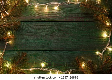 Photo of New Year's background with burning garland around perimeter, branches of spruce.