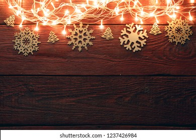 Photo of New Year's wooden red table with burning garland on top, snowflakes.