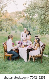 The photo of the newlyweds cutting their first piece of wedding cake together, while the guests are looking at it. The forest composition.
