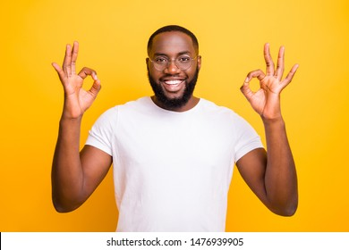 Photo of nice encouraged handsome smiling black man giving you ok sign with two hands simultaneously while isolated with vivid background