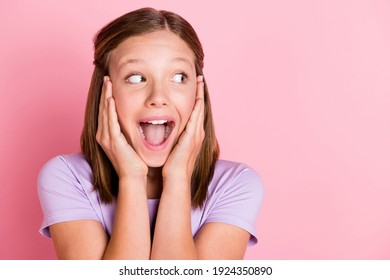 Photo of nice positive amazed little girl look empty space hold hands cheeks isolated on pink color background