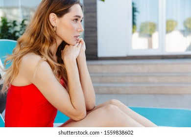 Photo of nice woman in swimsuit looking forward while sitting on chaise lounge near modern house outdoors