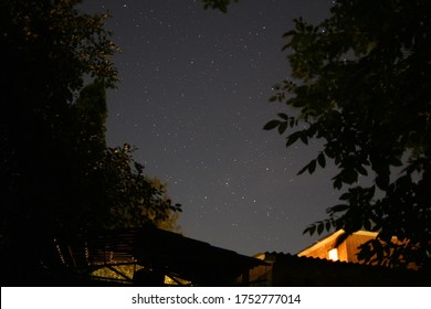 Photo of the night starry sky against the backdrop of houses and trees. Cassiopeia constellation at night.