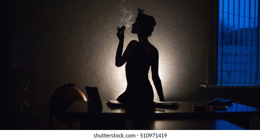 photo noir, retro, silhouette of a girl in front of a window with a blue light, a woman smoking a cigarette in the mouthpiece, a woman with a pen on head sitting on a table. globus, retro