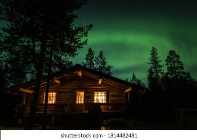 Photo of northern lights above a log cabin