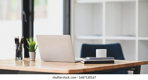 Photo of notebook, diary, coffee cup, pencil in vase, potted plant and computer laptop putting together on wooden working desk over modern living room windows and bookshelf as background.