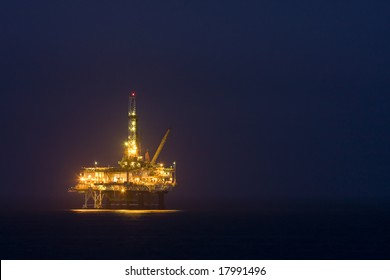 Photo of an offshore drilling rig off the coast of a city in the the US at night - landscape.