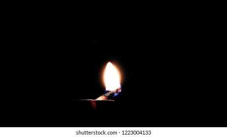 Photo of an oil lamp or diya(deepak) in the dark with the flame on it on the occasion of Diwali(Deepawali) in India.