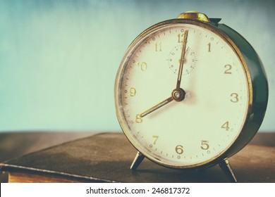 photo of old alarm clock over wooden table, with faded retro effect