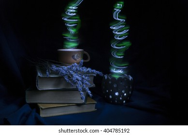 Photo of old books, flowers of lavender, cup of potion and magic lamp