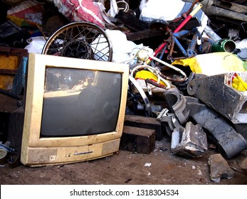 Photo of an old and broken computer monitor and other scrap materials at a junkyard