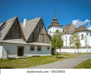 Photo of old house and big church in traditional village of Pribylina near Liptovsky Mikulas in Slovakia.