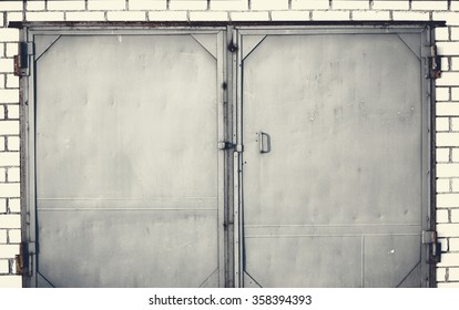 photo of an old iron door closed with brick wall