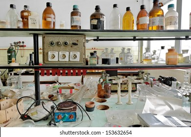 Photo of an old laboratory with a lot of bottles and dirt