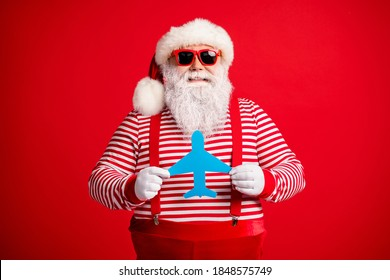 Photo of old man grey beard hold demonstrate showing blue paper plane funny wear santa claus x-mas costume suspenders sunglass striped shirt cap isolated red color background