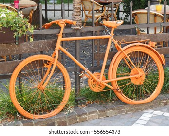 photo of old orange bike on the fence of the coffee shop