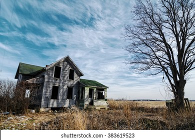 Photo of an old scary abandoned farm house that is deteriorating with time and neglect.  Enhanced with an old tree and a hangman's noose topped off with a dramatic  sky.