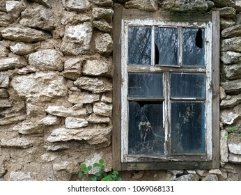 Photo of an old stone wall with a broken window.