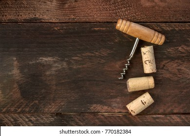 A photo of an old-fashioned corkscrew with corks, shot from above on a dark wooden background texture with a place for text. A design template for a wine list or a tasting invitation