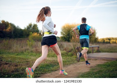 Photo on back of sportive woman and man running through park
