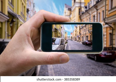 photo on the phone, the person photographed on a smartphone from the side. Street in the city center street in the Venetian style, the architecture of the Middle Ages. selfie