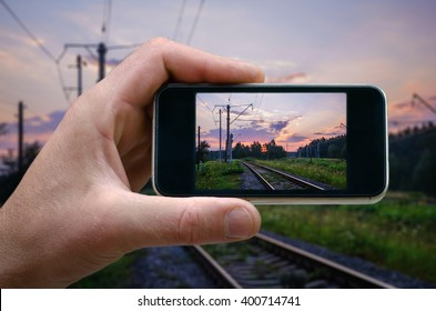 photo on the phone, the person photographed on a smartphone from the side. Railway on a background of the rising sun, the rails on the run. selfie