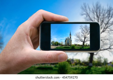 photo on the phone, the person photographed on a smartphone from the side. beautiful landscape with a standing Christian church. selfie