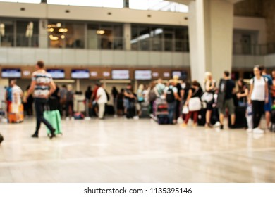Photo on purpose defocused shows people waiting for check in at the airport.