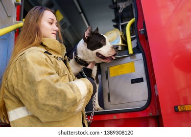 Photo on side of firewoman with dog standing near fire truck