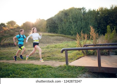 Photo on side of sportive woman and man running through park