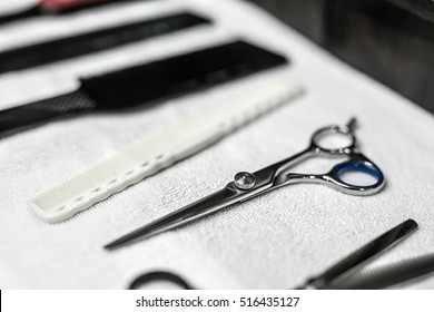 Photo on the wide aperture of the scissors and hair combs and hairbrushes. They lies on the white towel on the dark wooden background. Closeup. Horizontal.