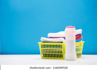 Photo of one bottle of cleaning powder and multi-colored towels in basket isolated on blue background