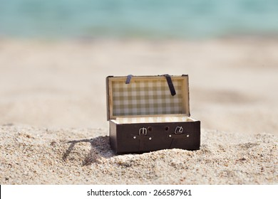 Photo Of Open Miniature Suitcase On Sunny Beach